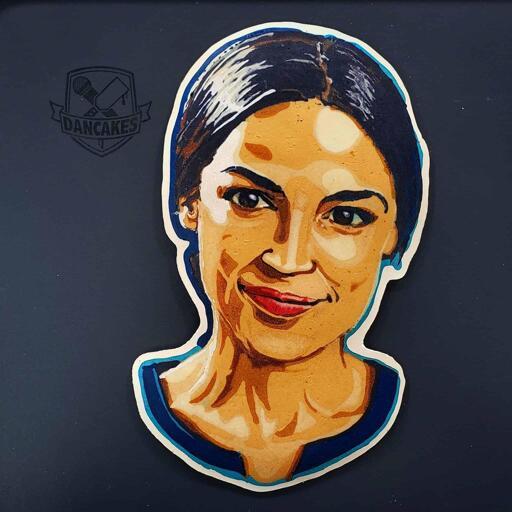 A photograph of a pancake art portrait of representative Alexandria Ocasio-Cortez, a united states politician and public figure. She is smiling, lips closed.